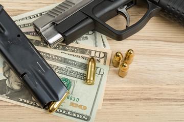 gun with bullet on US dollar banknotes