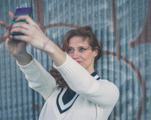Beautiful girl taking a selfie in an urban context