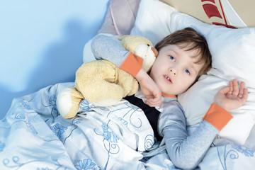 Portrait of a sick boy hugging a teddy bear