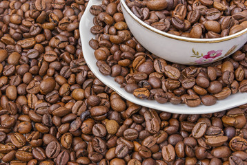 Cup and saucer filled with coffee beans