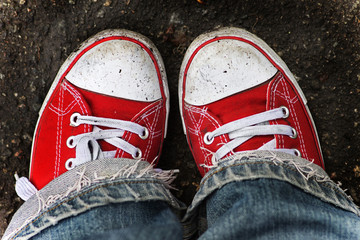 Wall Mural - Feet in dirty red sneakers and jeans outdoors.