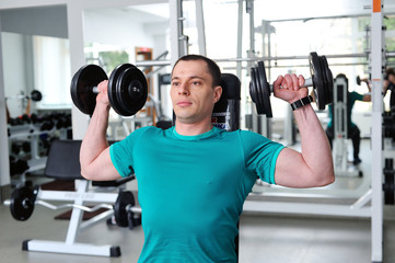 Man lifting dumbbells in a fitness club