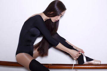 beautiful ballerina girl with dark hair posing in dancing hall