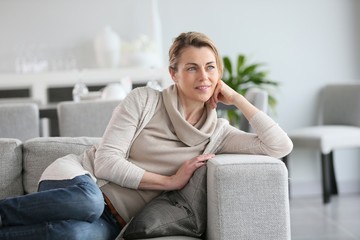 Mature woman relaxing on sofa at home