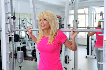 happy middle aged woman exercise with barbell