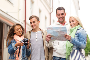 group of smiling friends with map and photocamera