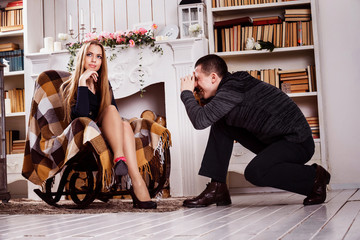 A cheerful man is taking photo of a young beautiful girl in stud
