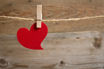Red fabric heart hanging on the clothesline . On wooden backgrou