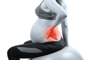 Pregnant woman on gymnastic ball holding her back in pain