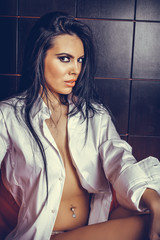 Portrait of sensual brunette young woman in man's shirt  posing