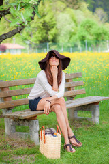 Woman with a sunhat sitting on a bench