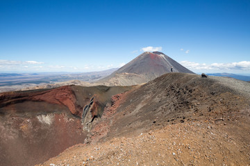 Hiker next to red crater