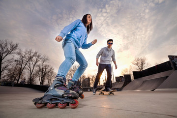 Girl on rollerblades and boy on skateboard in skate park