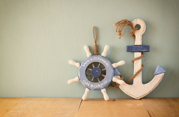 old nautical wood wheel and anchor on wooden table over wooden a