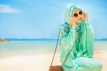 pretty girl on a beach wearing traditional muslim costume