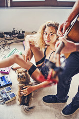 beautiful sexy girl watching her boyfriend playing guitar