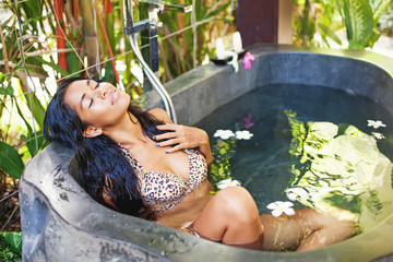 Beautiful exotic woman having bath in a luxury spa salon