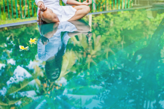 Woman meditating at pool side. Reflection in the water
