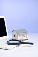 portrait of magnifying glass, model house and laptop