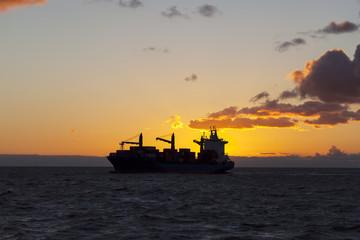 Ship underway at sunset