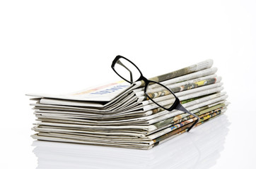 glasses on newspaper with white background