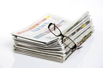 bird eye view of glasses on newspapers against white background