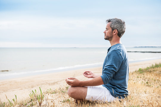 An attractive man is sitting face to the ocean in lotus position