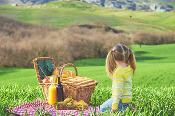 Little girl reversed back doing a picnic in the countryside of T