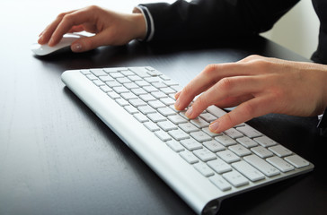 Female hands working at a keyboard. Shallow DOF.