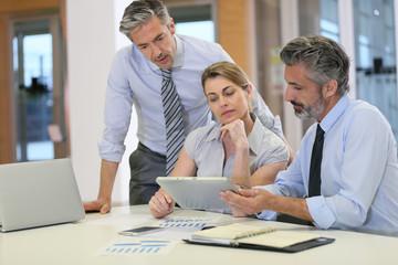 Sales people meeting in office, using tablet