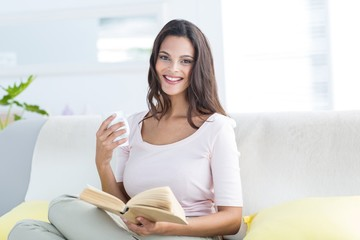 Beautiful brunette holding mug and reading a book