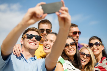group of friends taking selfie with cell phone