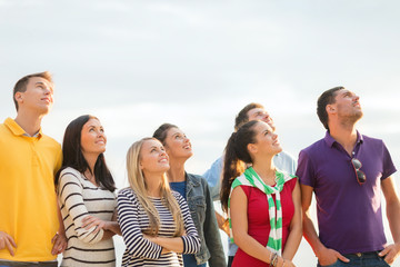 group of happy friends looking up on beach