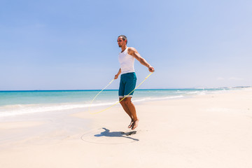 handsome man skipping on the beach
