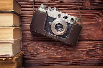 Vintage 35mm Film Camera and Stack of Books Over Wooden  Backgro