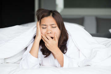 Sleepy asian woman yawning in bed at home