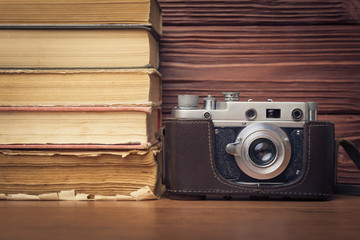 Vintage Camera and Stack of Books Over Wooden  Background