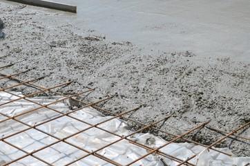 Wet concrete cement flowing over rebar metal