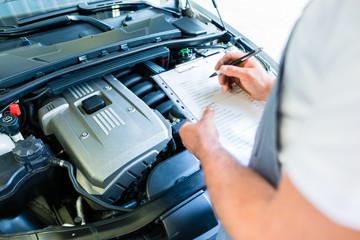 KFZ-Mechaniker mit Checkliste in Autowerkstatt