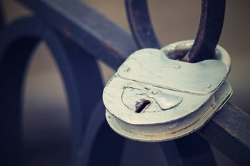 padlock on an iron fence with a retro effect