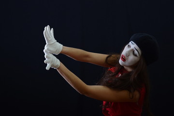 the girl is MIME wears white gloves .on a dark background