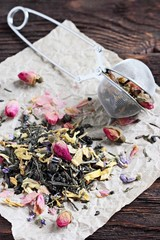 Green tea with dried flowers on a wooden table.