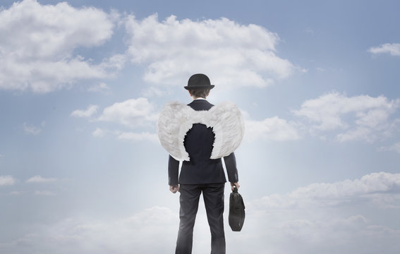 Business angel against blue sky with copy space