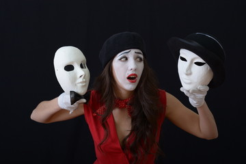 the girl is MIME holding a theatrical mask in hats