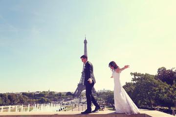 Bride and groom walking near fountain in Paris