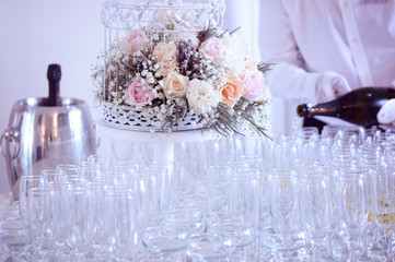 Many glasses of champagne with birdcage flower decor