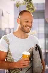 Happy man walking on street holding coffee