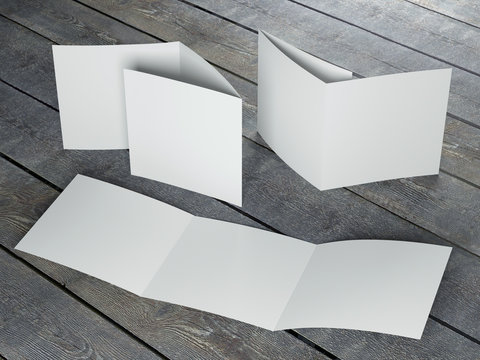 Blank template of trifold square brochure on wood floor