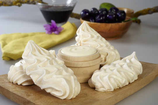 Wooden board with meringues and a bowl of cream.