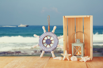 Old nautical wood wheel and shells on wooden table over sea back